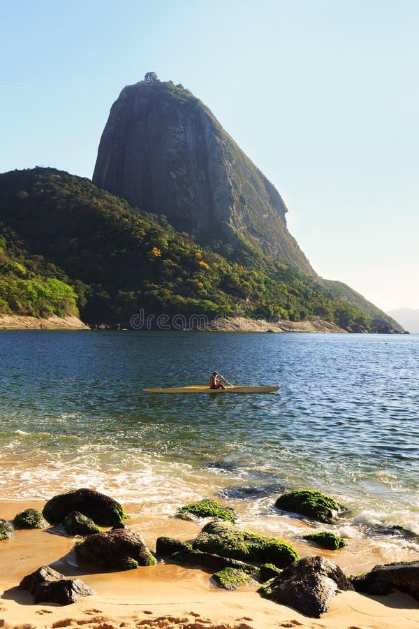 山Sugarloaf红色海滩海沙人冲浪的独木舟,里约de 免版税库存图片