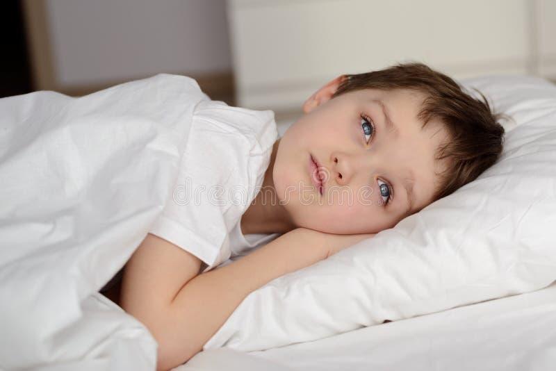 7岁休息在与眼睛的白色床上的男孩打开 免版税库存图片