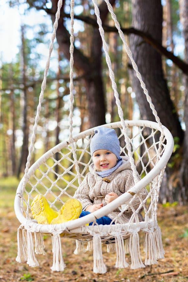 3岁哄骗摇摆在一把垂悬的椅子户外 库存照片