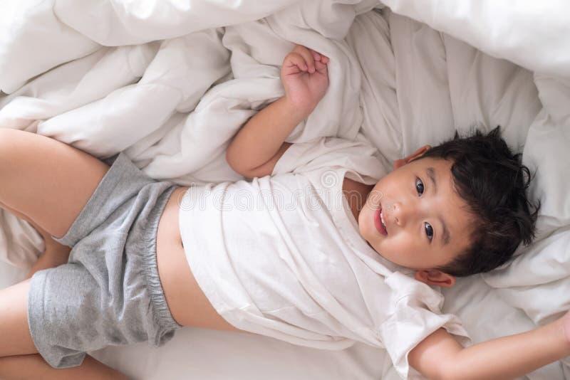 3岁小逗人喜爱的亚裔男孩在家在床,孩子说谎上 免版税库存照片