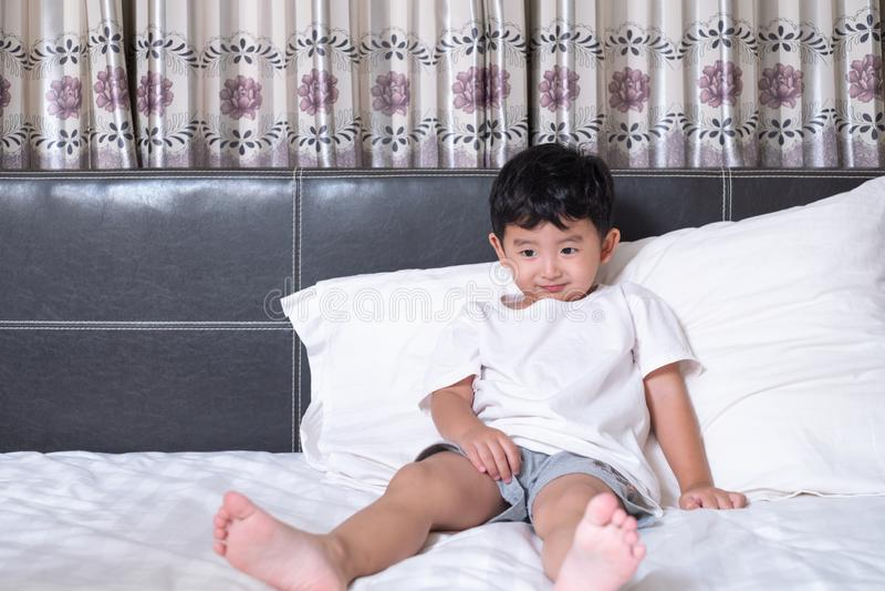3岁小逗人喜爱的亚裔男孩在家在床,孩子说谎的使用和微笑上在与枕头和毯子的白色床上,与 库存图片