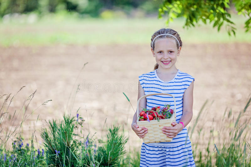 7岁拿着篮子的女孩有很多草莓 免版税库存图片