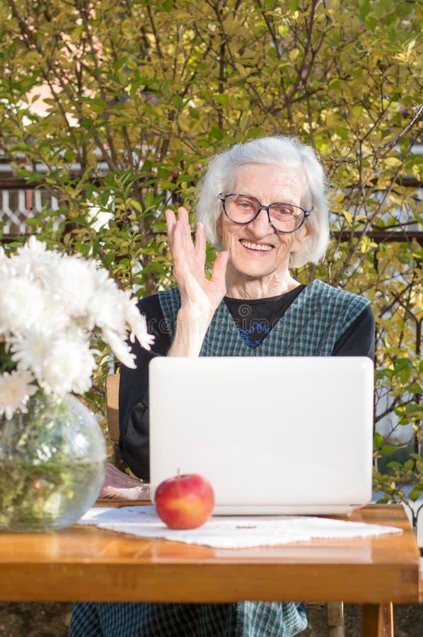 90岁挥动的妇女,当有录影电话时 库存照片