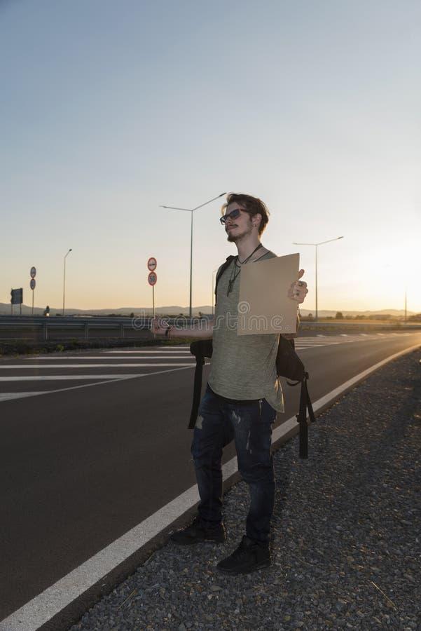 21岁搭车在高速公路的人 库存图片