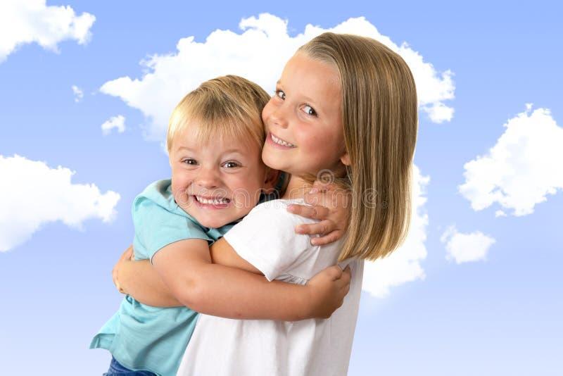 7岁摆在与她小的3岁的可爱的白肤金发的愉快的女孩在与云彩的蓝天隔绝的兄弟微笑的快乐 免版税图库摄影