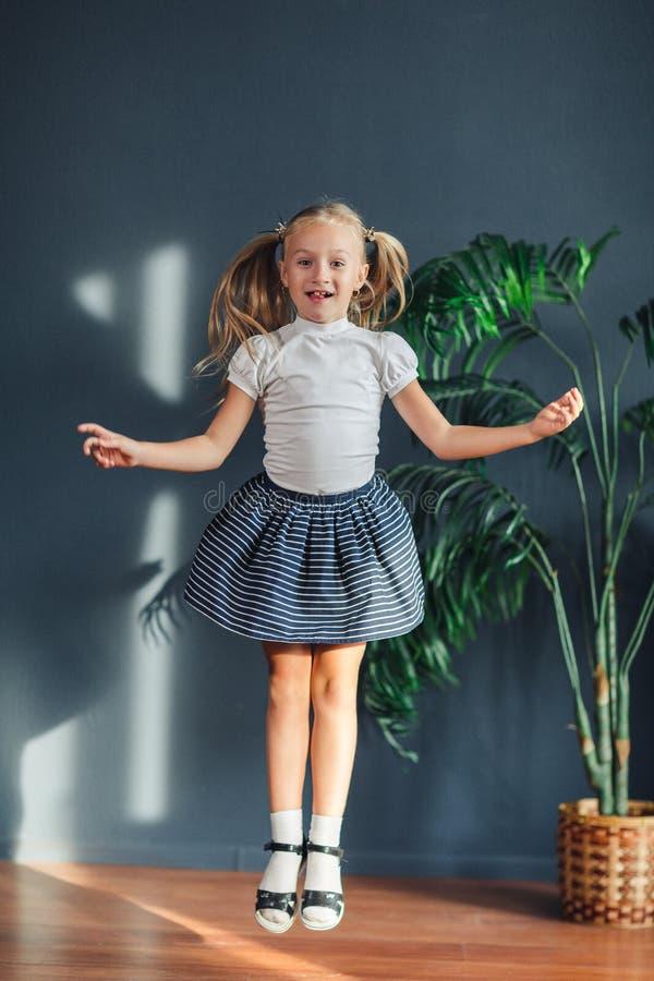 8岁有在尾巴、白色T恤、白色袜子和灰色裙子会集的头发的美丽的矮小的白肤金发的女孩跳跃在孩子 库存照片