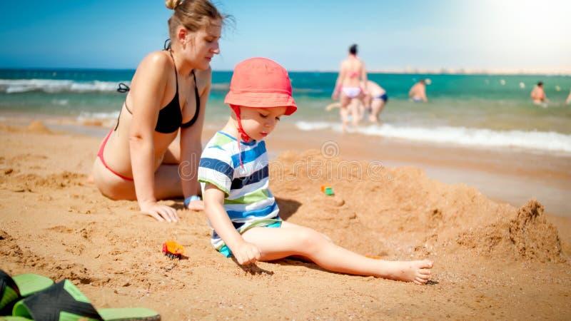 3岁照片小孩男孩大厦与年轻母亲的沙子城堡海洋海滩 获得的家庭放松和乐趣 库存图片