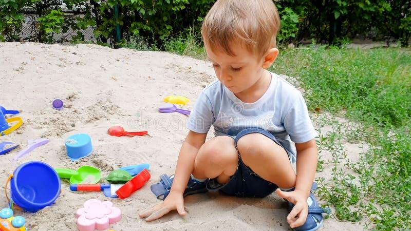 3岁特写镜头照片使用与在沙盒的玩具的小孩男孩在操场 免版税库存照片