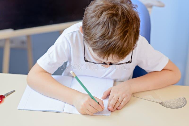 7岁男孩解决在他的习字簿的乘法表 免版税库存照片