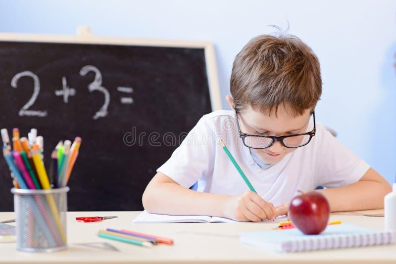 7岁男孩解决在他的习字簿的乘法表 库存照片