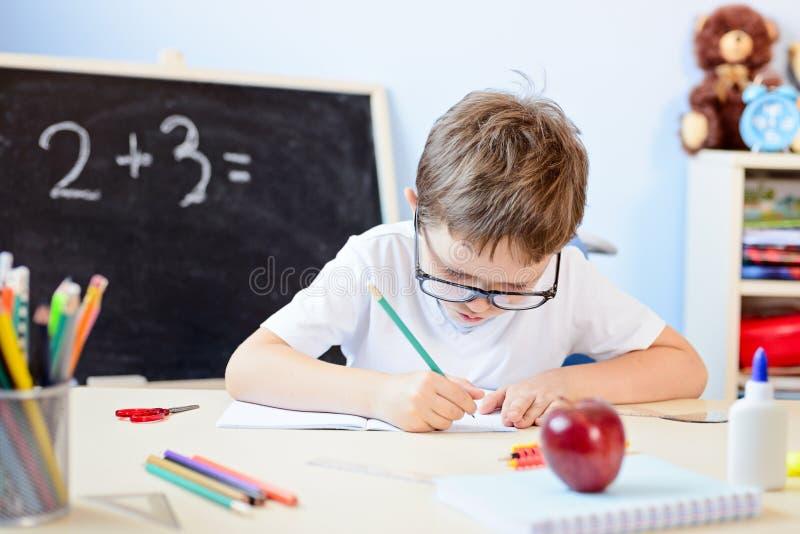 7岁男孩解决在他的习字簿的乘法表 免版税库存图片