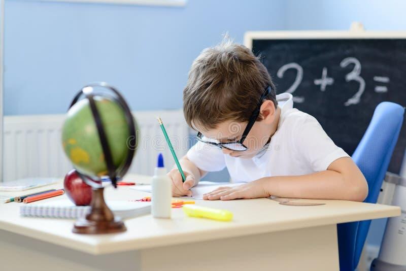 7岁男孩解决在他的习字簿的乘法表 库存图片