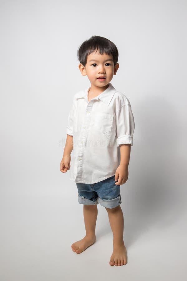 2岁画象男孩穿戴白色衬衣和短裤斜纹布在白色背景 库存照片