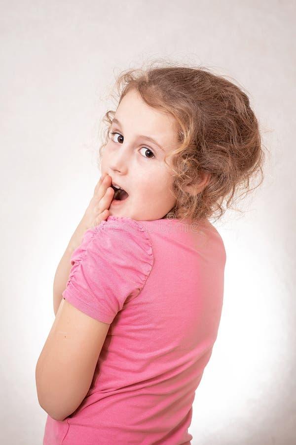 8岁的一逗人喜爱的情感女孩的接近的画象与卷发,灰色背景的 免版税图库摄影