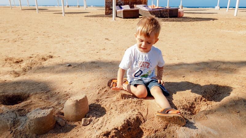3岁的图象小小孩男孩坐海海滩和修造的城堡从湿沙子 免版税库存照片