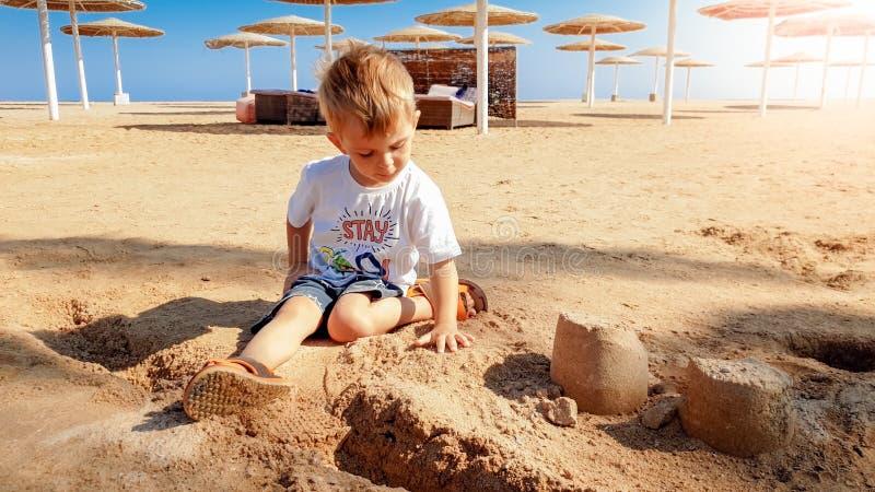 3岁的图象小小孩男孩坐海海滩和修造的城堡从湿沙子 免版税库存图片