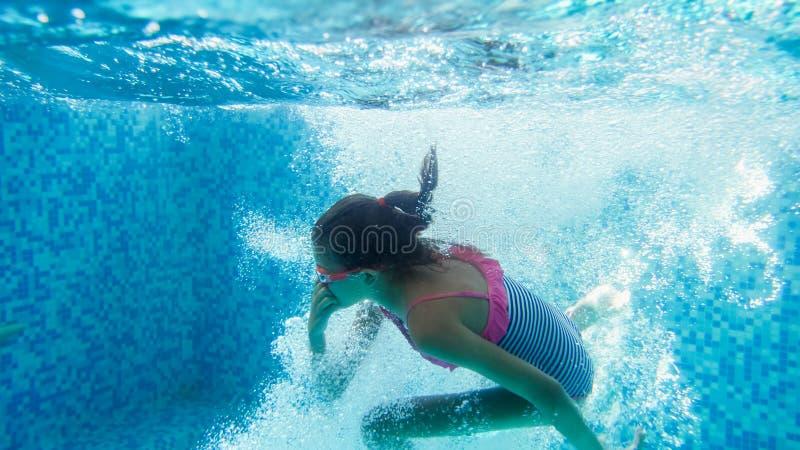 10岁的水下的特写镜头图象女孩游泳和潜水在游泳场 免版税库存图片