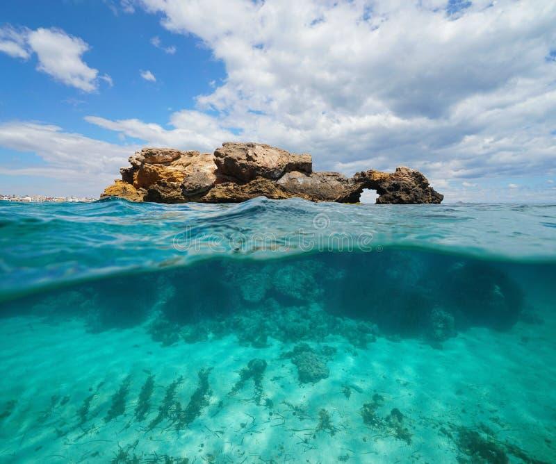 岩层分裂在水表面,陆间海上下的视图一半 库存照片