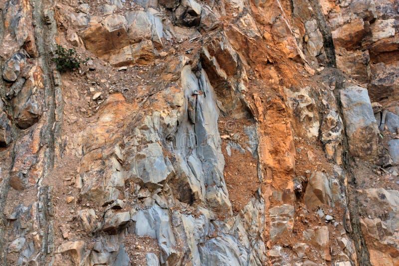 岩石分层堆积-岩石的五颜六色的形成被堆积在上百年 与引人入胜的纹理的有趣的背景 库存图片