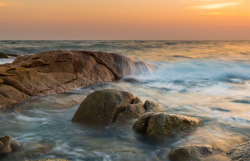 岩石和光滑的海波浪在日落时间 免版税库存照片