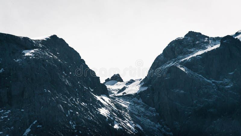 岩石和多雪的山美丽的射击与使清楚的天空惊奇的在背景中 免版税库存照片