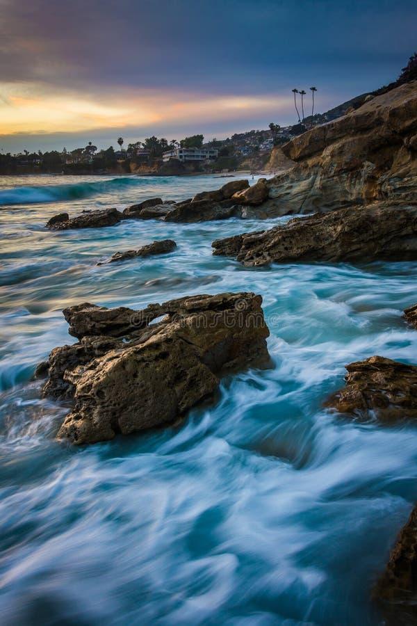 岩石和波浪在日落的太平洋 免版税图库摄影