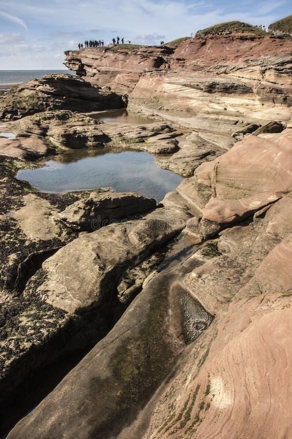岩石和游人峭壁的在Hilbre海岛,西部柯尔比, Wirral,英国 免版税图库摄影