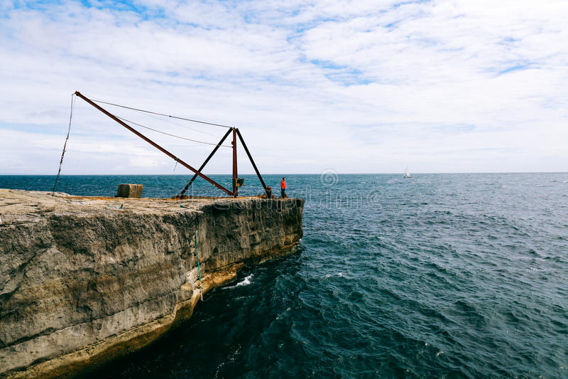 岩石和生锈的钢渔夫` s在波特兰比尔灯塔附近抬头 免版税库存照片