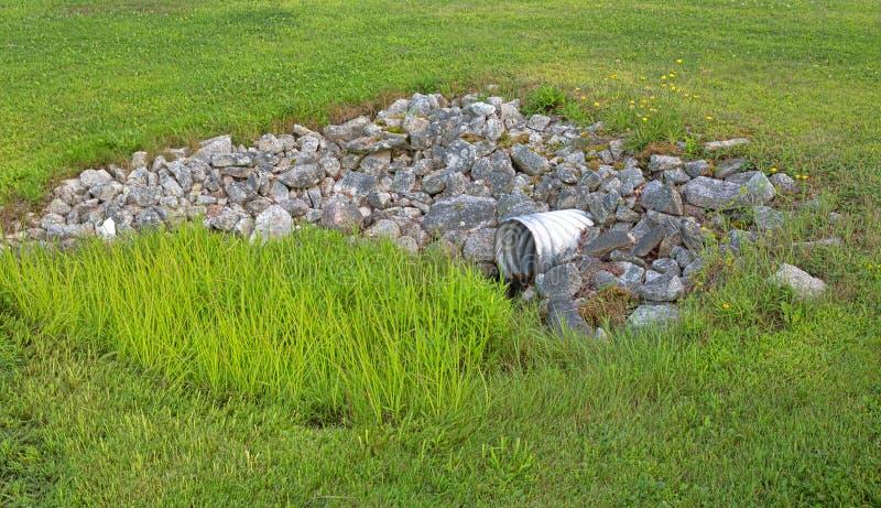 岩石和草围拢的风暴阴沟 免版税库存图片