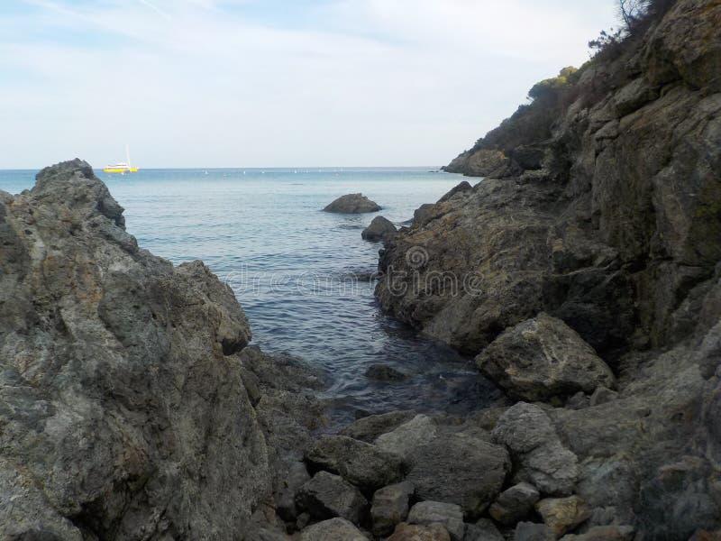 岩石和蓝色海有一条遥远的黄色小船的 免版税库存图片