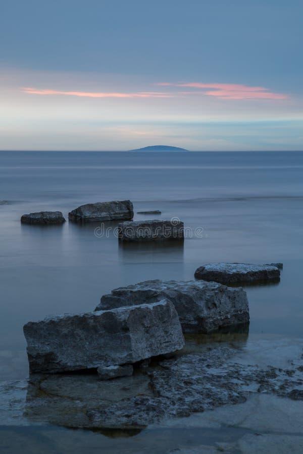 岩石在日落以后的柔滑的光滑的水中 库存照片