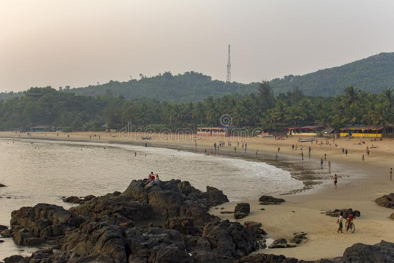 岩石在沙滩附近的海与基于和游泳背景的人  免版税库存图片