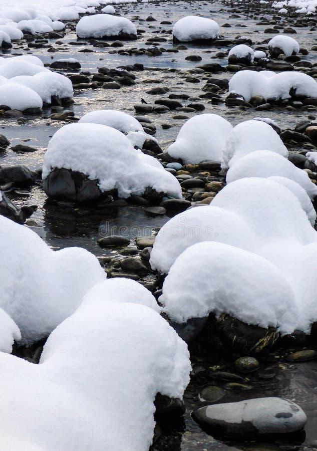 岩石在雪盖的河在深刻的冬天 图库摄影