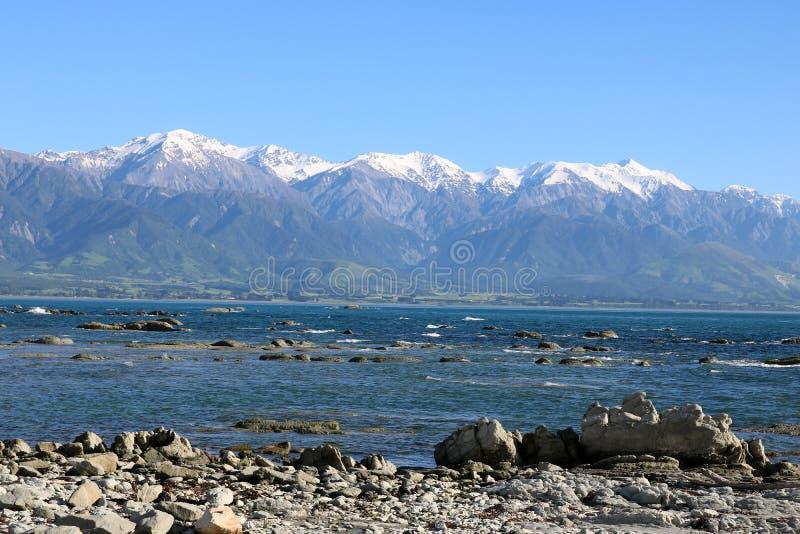 岩石岸海和雪加盖了山Kaikoura 图库摄影