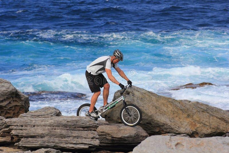 岩石岸的极端骑自行车的人 免版税库存图片