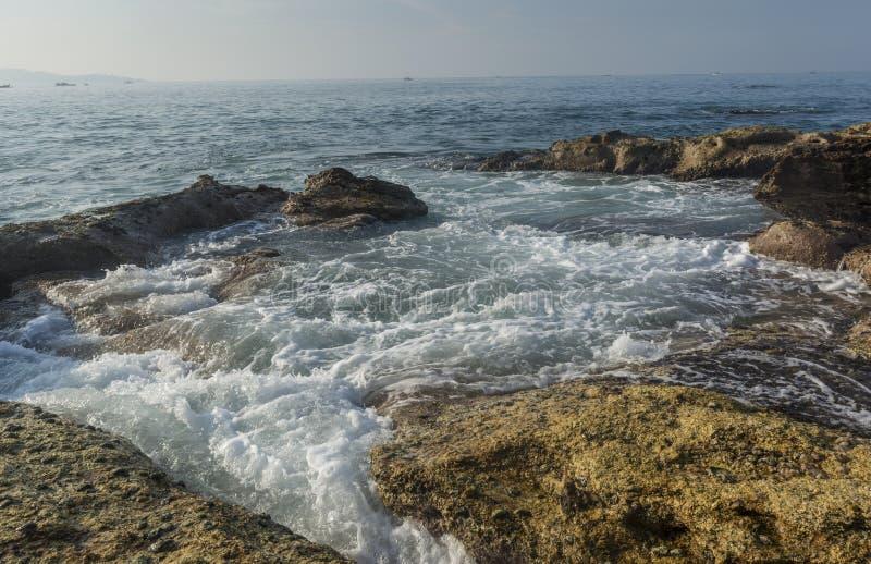 岩石岸美好的惊人的风景与波浪的在韦利格默镇的海滩 图库摄影