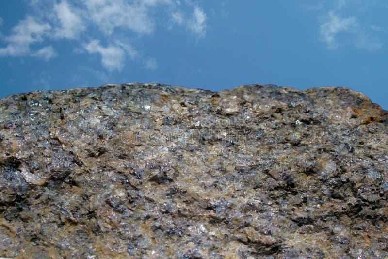 岩石或石头在天空蔚蓝有云彩背景 花岗岩crouan外缘或采撷边缘象峭壁或山 地质矿物纹理 库存照片