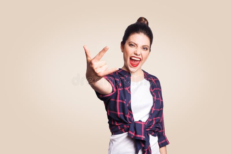 岩石标志 显示与手指的愉快的滑稽的暴牙的兴高采烈的少妇岩石标志 在米黄背景射击的演播室 免版税图库摄影