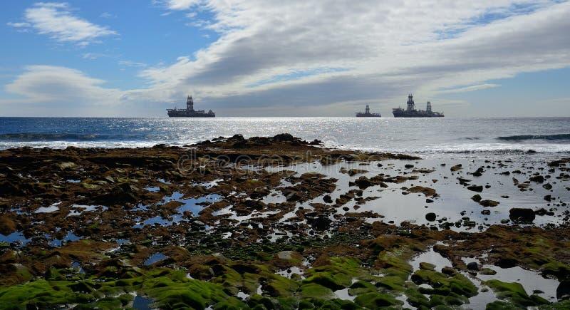 岩石海岸和石油平台 库存照片