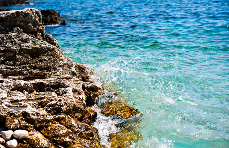 岩石海岸用在蓝色海前面的飞溅水 库存照片