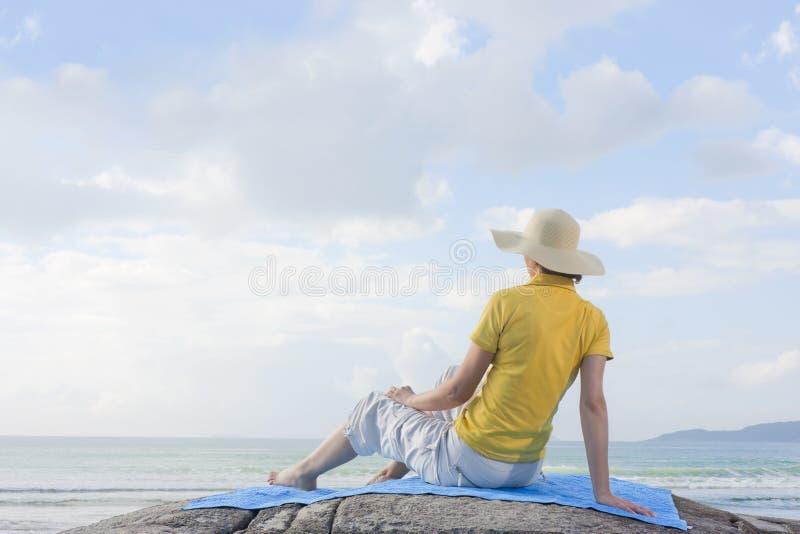 岩石海运坐的妇女 图库摄影