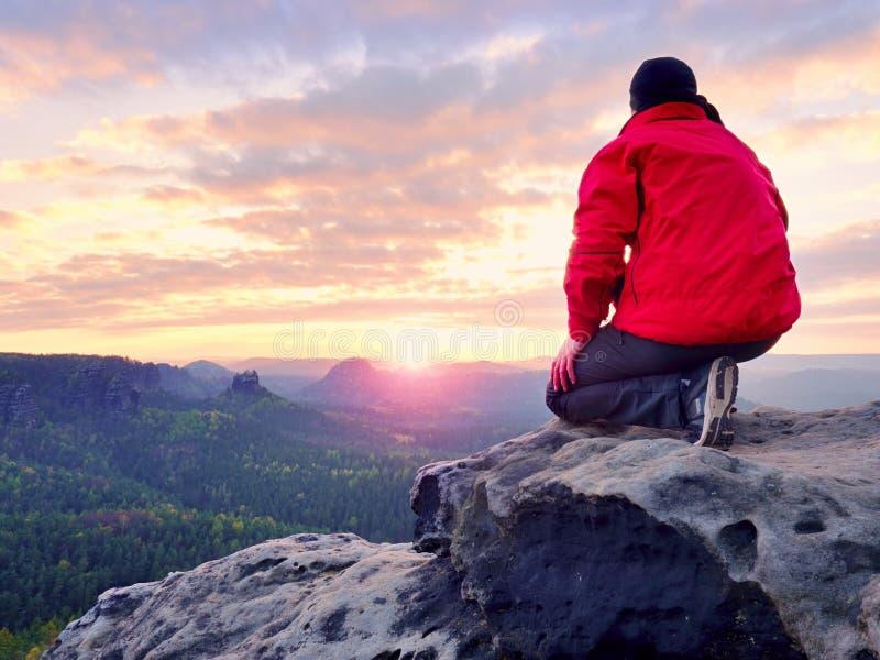 岩石的坐的远足者 红色黑温暖的衣裳的人坐峭壁并且享受远的看法 库存照片