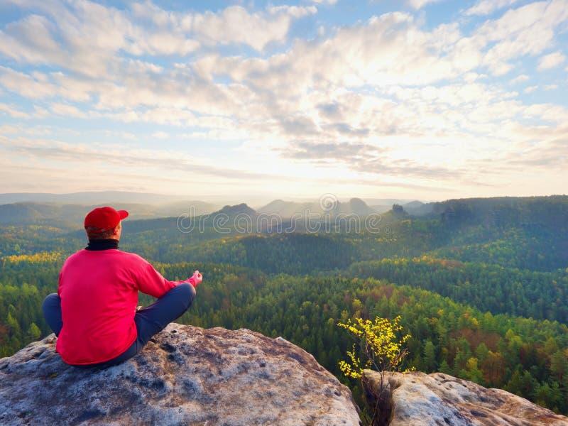 岩石的坐的远足者 红色黑温暖的衣裳的人坐峭壁并且享受远的看法 库存图片