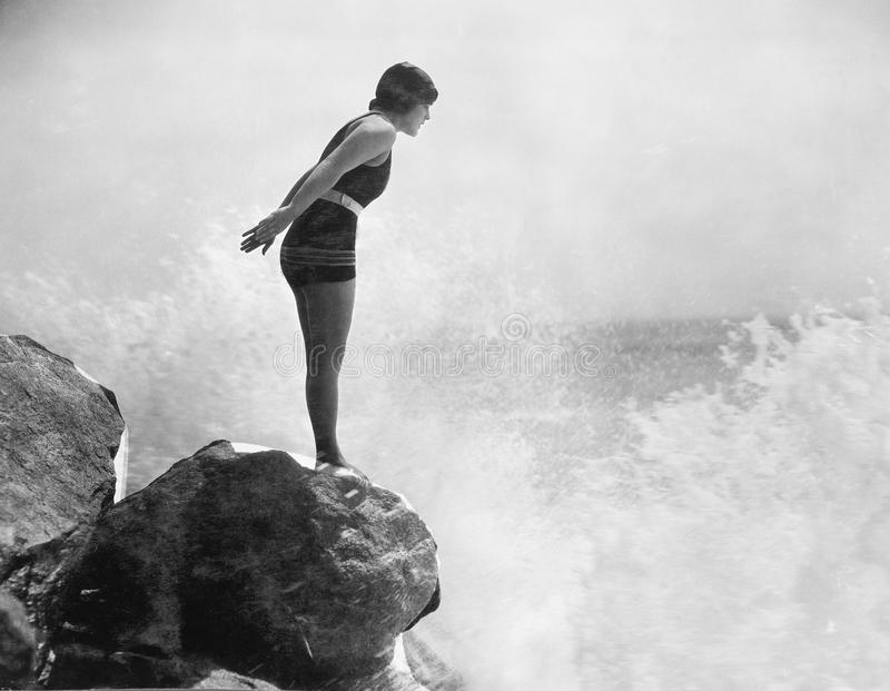 岩石的女性游泳者在碰撞的海浪上(所有人被描述不更长生存,并且庄园不存在 供应商保单 免版税库存照片