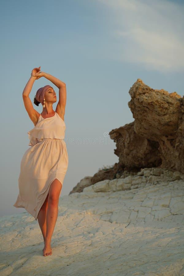 岩石的妇女由日落 库存照片
