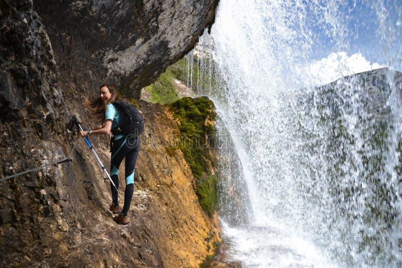 岩石的妇女登山人由瀑布 免版税库存照片