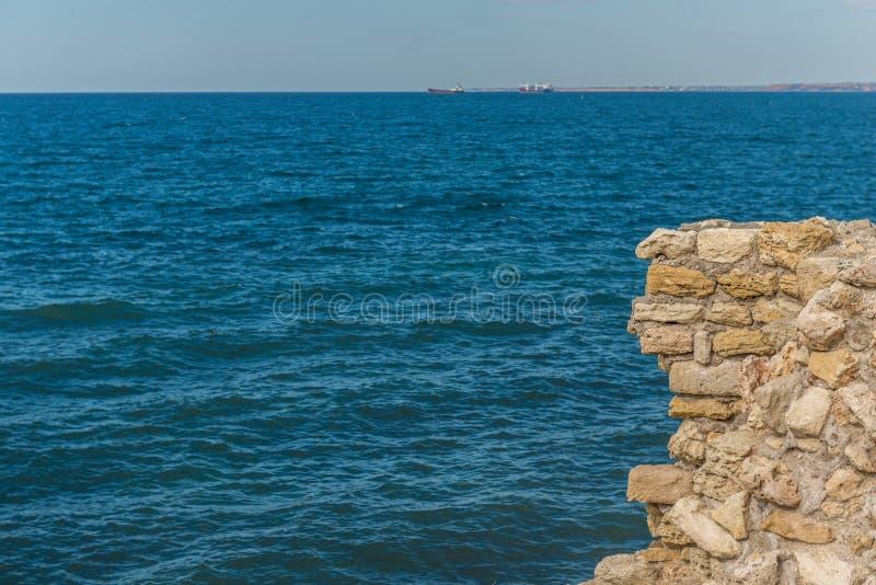 岩石的老堡垒在海上 在古老的岩石峭壁在上面 黏附在外面的石冰砾 库存图片
