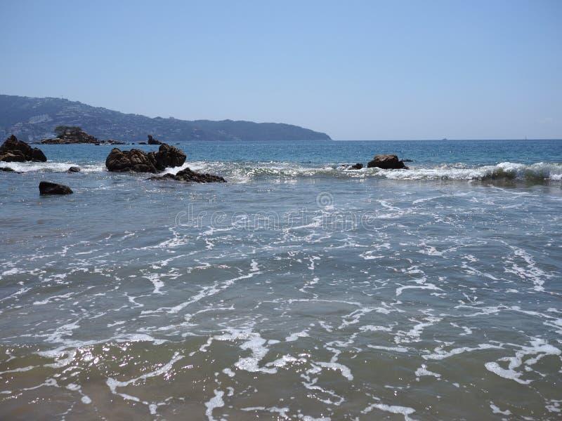 岩石美妙的看法在阿卡普尔科市海湾的在有太平洋波浪的墨西哥在沙滩风景 库存照片
