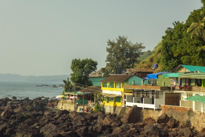 岩石背景的五颜六色的房子在小山的与以海洋为背景的绿色树 库存图片