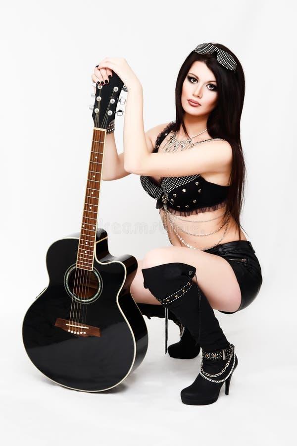 岩石衣裳的时尚妇女有吉他的 库存图片